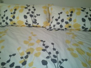 Bed with a cream bedspread with a yellow and grey floral pattern