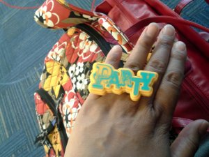 """Roshaunda wearing a ring that was used as a cupcake decoration.  The ring reads """"Party."""""""