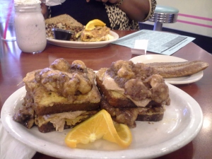 French toast, made with gluten-free bread, smothered in cinnamon sauce, cream cheese frosting, and bananas foster