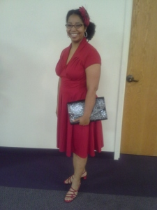 Roshaunda wearing a retro red dress with a red flower in her hair, red strappy sandals, and a black and grey snake skin print clutch