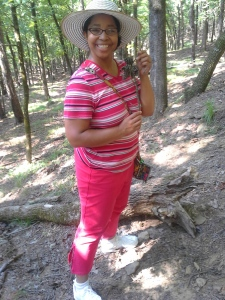 Me in my hiking gear - cross body purse and sun hat - holding a pinecone sprig