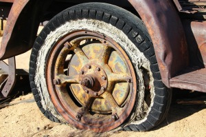 Rusty, flat tire.  Image by nightowl on Pixabay at https://pixabay.com/en/tire-wheel-vintage-antique-old-416189/