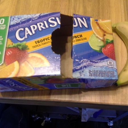 Carton of CapriSun next to a bruised banana