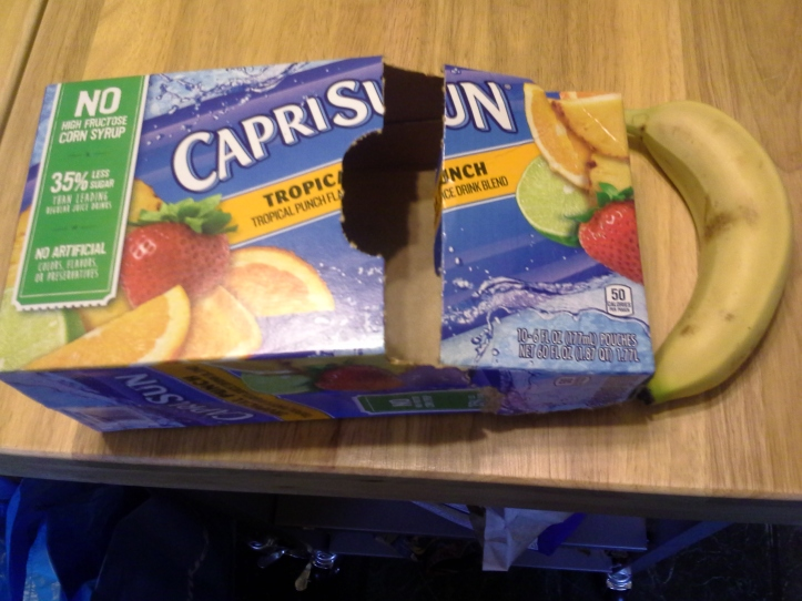Carton of CapriSun next to a bruised banana