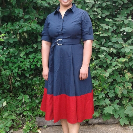 Roshaunda in a retro style navy and red dress, red flower hair pin, and pink flip-flops