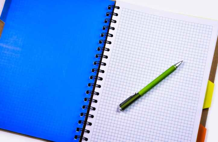 green and silver push pen on white ruled paper indoors